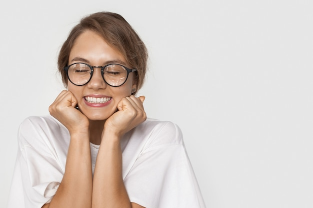 여유 공간이있는 흰 벽에 선물을 기다리는 안경 백인 여자의 흑백 사진