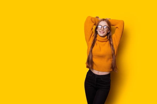Монохромное фото рыжей дамы с веснушками и очками, позирующей с поднятой рукой на желтой стене