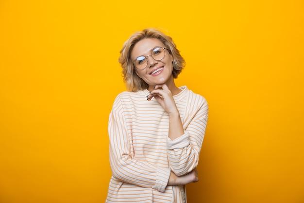 Монохромное фото кавказской блондинки в очках и улыбающейся камеры, касающейся ее подбородка на желтой стене студии