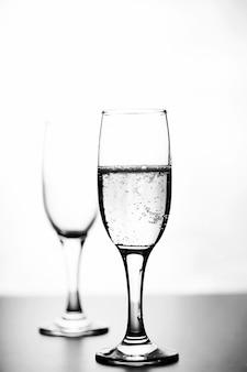 白い背景の分離の白いテーブルの上のシャンパンのモノクロ写真
