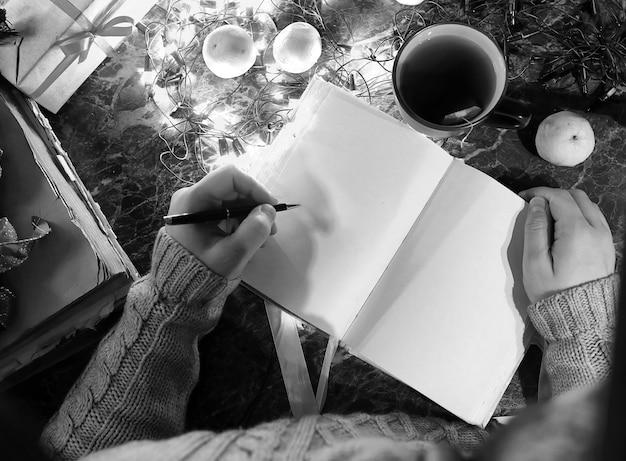 装飾が施された新年のテーブルのために彼の手に白紙の本を持っている男のモノクロ写真
