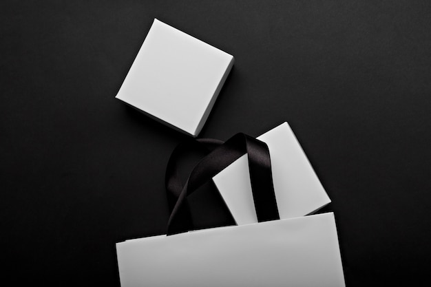 Monochrome photo of a white paper bag and boxes on a black background. place for your logo branding