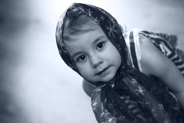 ハンカチと踊るドレスを着た少女のモノクロ写真