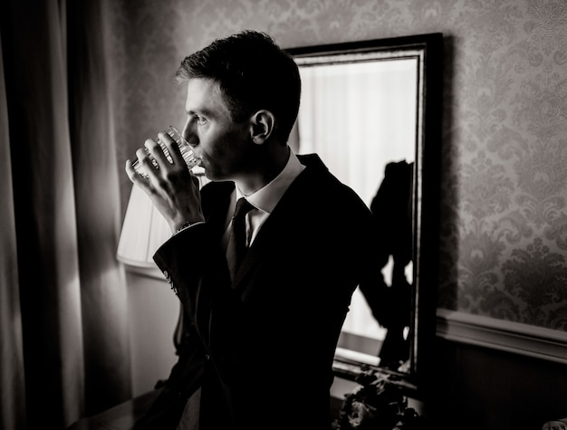 Monochrome portrait of handsome young man in room is drinking dressed in suit