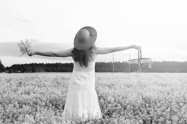 Монохромный портрет молодой девушки в шляпе, стоящей в огромном поле цветов
