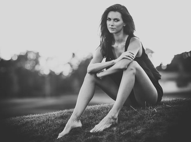 Монохромный портрет молодой девушки, сидящей на траве
