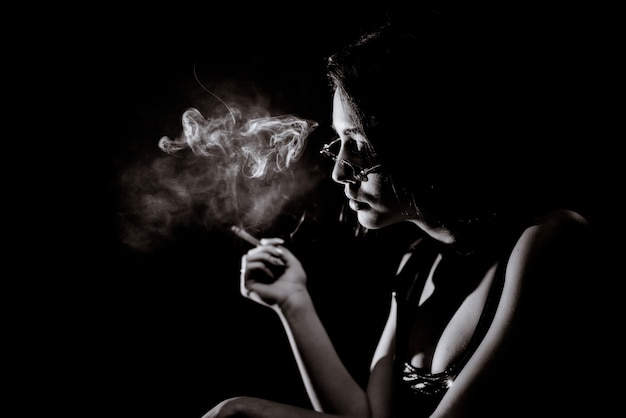 Монохромный портрет молодой девушки, которая курит с большим декольте и в очках