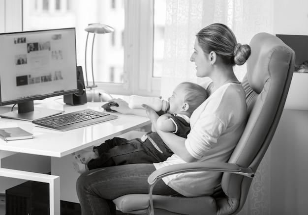 オフィスのテーブルで彼女の赤ちゃんを養う若い母親のモノクロの肖像画