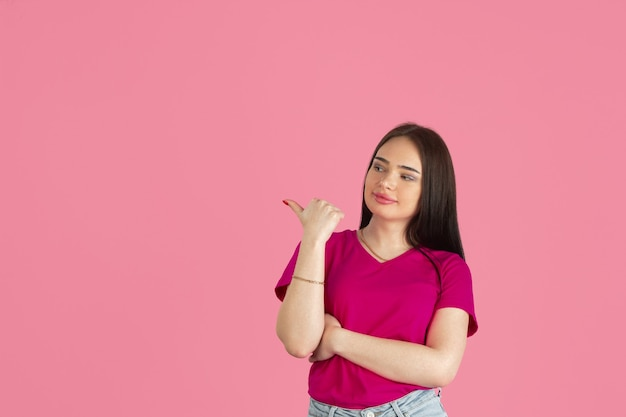 Monochrome portrait of young caucasian brunette woman on pink wall