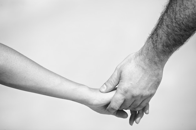 Monochrome shot of couple holding hands with shallow depth of field