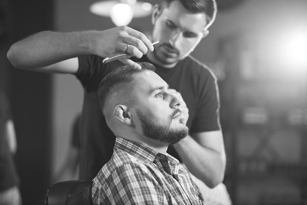 이발소에서 전문 이발사로 머리를 자르는 젊은 잘 생긴 남자의 흑백 샷.