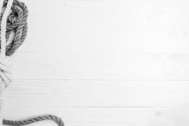 海の結び目と白い木の板の上に横たわるロープのモノクロ ショット
