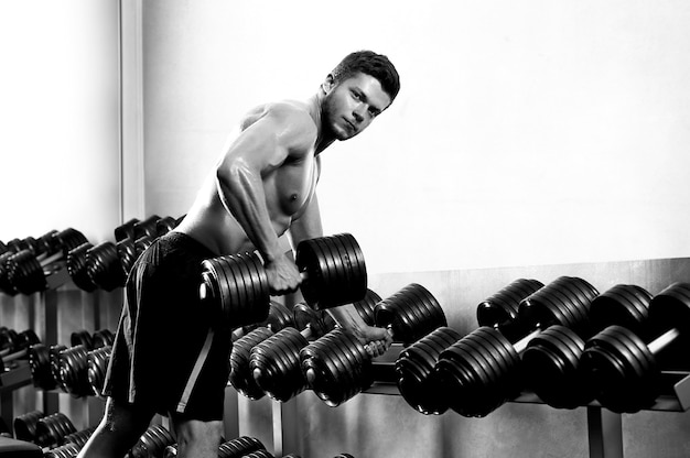 Monochrome shot of a ripped shirtless man exercising