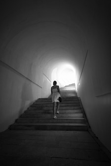 Monochrome shot woman going up the stairs at tunnel with light in the end