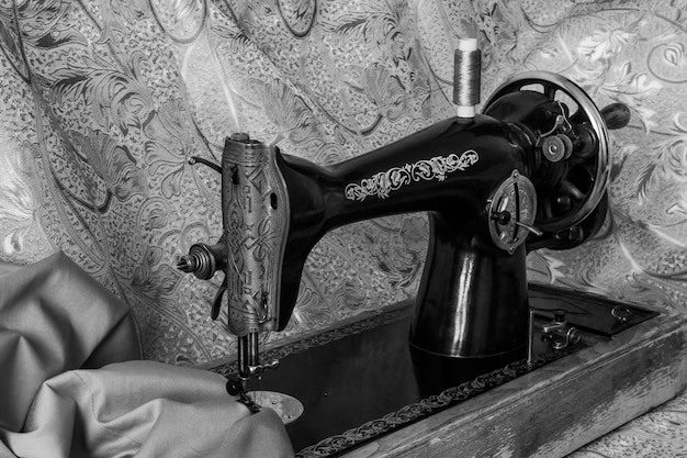 Monochrome still life with antique sewing machine and cloth