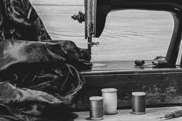 Monochrome still life with antique sewing machine and a variety of sewing accessories