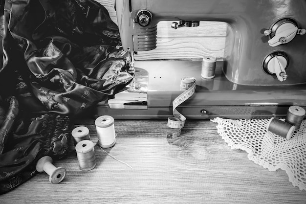 Monochrome still life with vintage electric sewing machine, fabrics and spools of thread