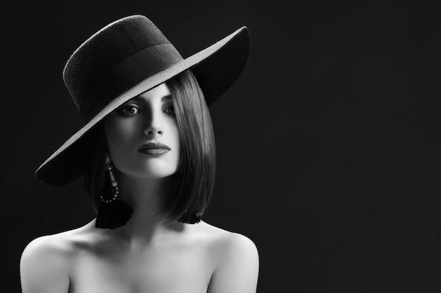 넓은 모자 copyspace를 입고 관능적으로 포즈를 취하는 우아한 젊은 여성의 흑백 스튜디오 샷 복고풍 빈티지 구식 세련된 아름다움 메이크업 빨간 입술 갈색 머리 섹시한 유혹 개념.