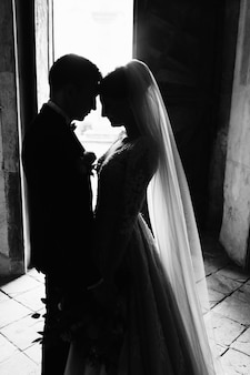 Monochrome tender photo of a wedding couple who is nearly kissing