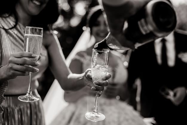 Vista monocromatica di una bottiglia di versamento in bicchieri e bicchieri di champagne nelle mani delle donne tenere