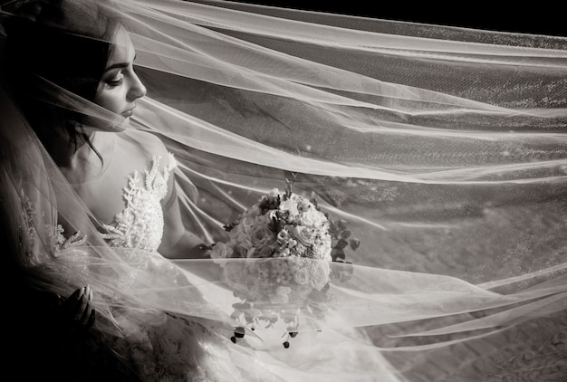 Monochrome view of a tender beautiful bride with wedding bouquet and long veil with closed eyes