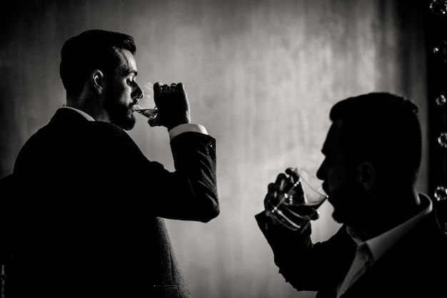 Monochrome view of two men who are drinking alcohol drinks indoors