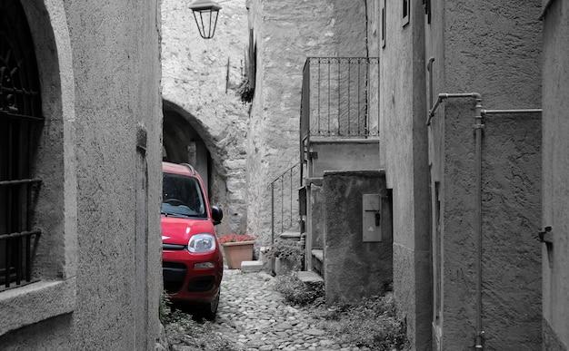 이탈리아의 흑백 거리에서 단색 빨간 차