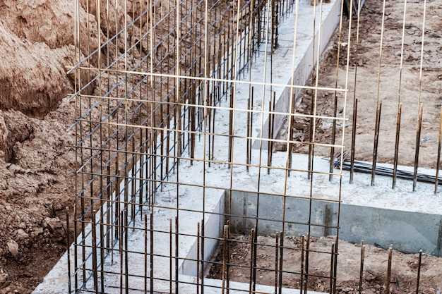 Monolithic foundation with metal reinforcement. forms vertical formwork structures for the basement of a residential building. monolithic concrete foundation. support foundation. home construction.