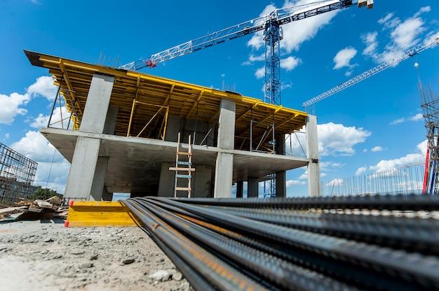Монолитный каркас с металлической фурнитурой строящегося нового дома на фоне крана и голубого неба.