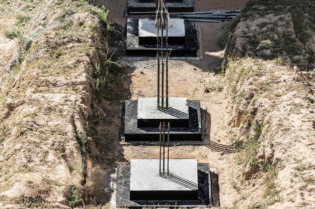 住宅建築用のモノリシック鉄筋コンクリート基礎。建設現場でのグリル。基礎のある建設ピット。