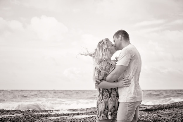 Monotone shot of a happy couple in love kissing on the beach at summer time, vintage style