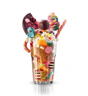 Monster shake, freak caramel shake isolated. colourful, festive milk shake cocktail with sweets, jelly. colored caramel milkshake array of different child sweets and treats in glass. sweet milkshake