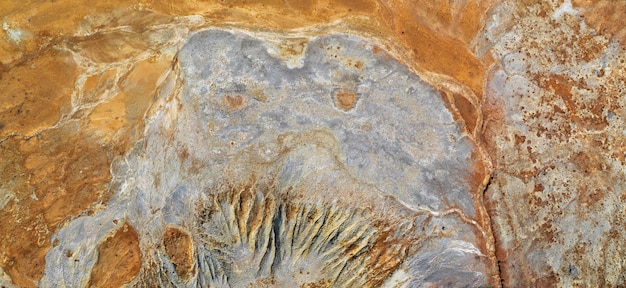 녹슨 주황색 배경 위에 괴물 모양의 회색 얼룩이 있습니다. 오래된 구리 광산의 자연 질감