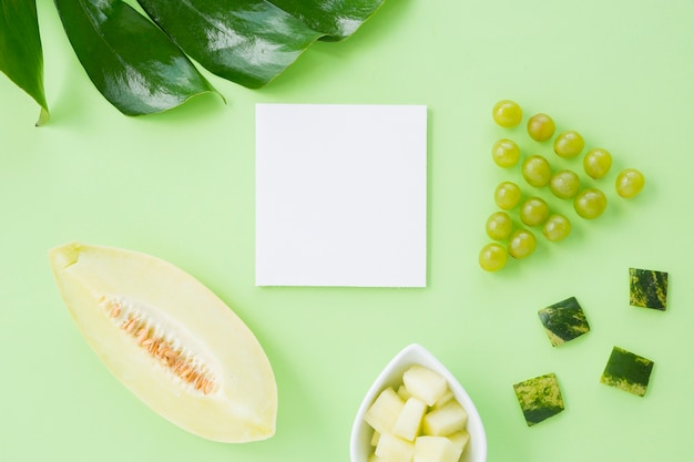 Monstera leaf; grapes; muskmelon on white paper against pastel background