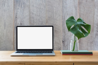 Monstera leaf in glass bottle over the books and laptop with white screen