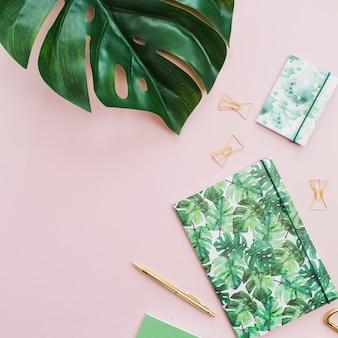 モンステラの葉、ノート、ペン、ピンクの表面にトロピカルパームスタイルで作られたはさみ