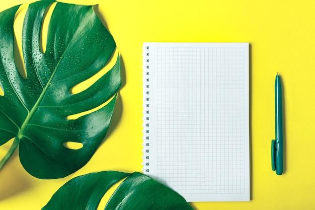 몬스테라 잎, 체크 무늬 공책, 세련된 노란색 배경에 펜. 복사 공간