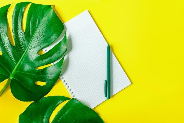 Листья монстеры, клетчатый блокнот и ручка на модном желтом фоне. копировать пространство