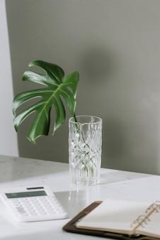 モンステラ熱帯のヤシの葉が静止したオフィスのテーブルの上に立っているガラスの花瓶に