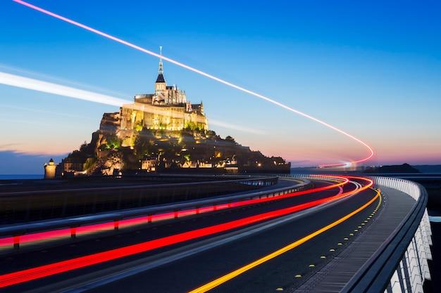 Mont saint michel at dusk with bus light, normandy. france