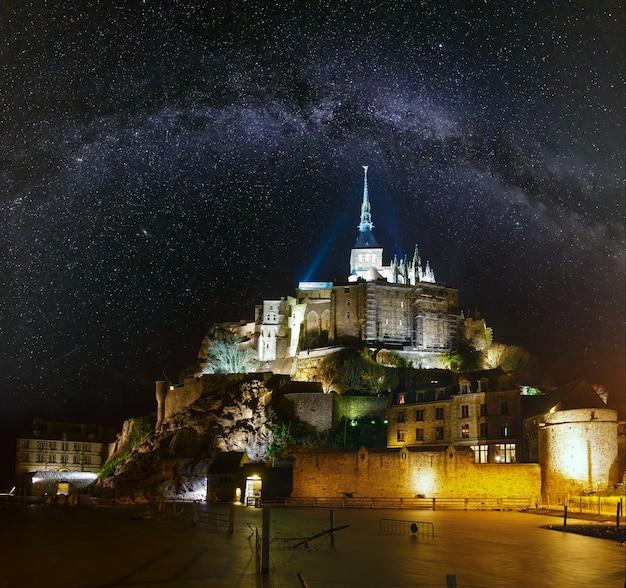 Мон-сен-мишель, ночная точка зрения франции и звездный млечный путь в небе. построен в xi-xvi вв. главный фасад церкви 12 века постройки. архитектор уильям де вольпиано.