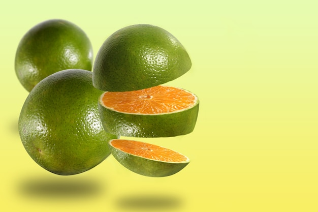 Montage with three oranges fruits, one cut and two whole, with yellow background.