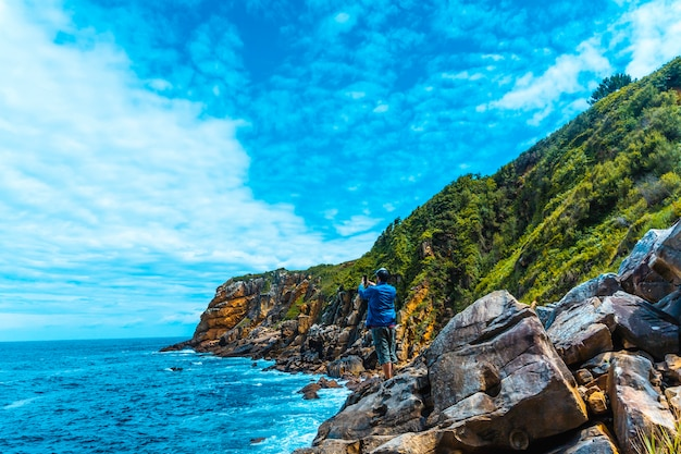 Monte ulia in the city of san sebastián, basque country. visit the hidden cove of the city called illurgita senadia or illurgita senotia. a young man in a blue jacket taking a photo with his mobile