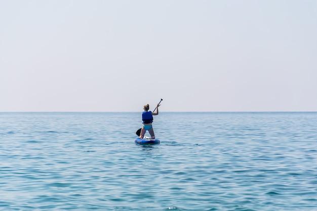 Черногория, будва. туристы занимаются греблей на доске (sup) на поверхности спокойного моря.