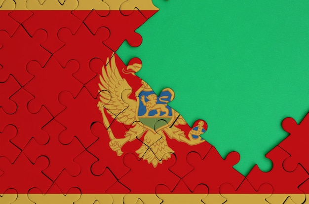 몬테네그로 깃발은 오른쪽에 무료 녹색 복사 공간이있는 완성 된 직소 퍼즐에 그려져 있습니다.