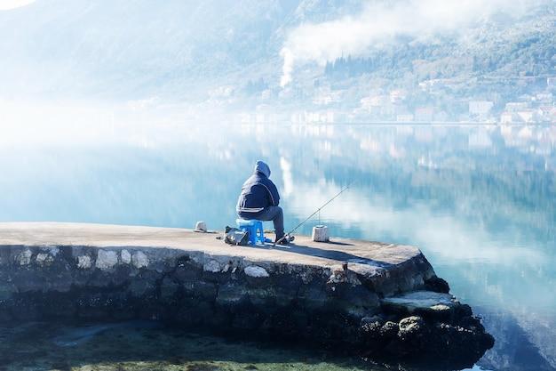 Черногория, которский залив, мужчина ловит рыбу на берегу
