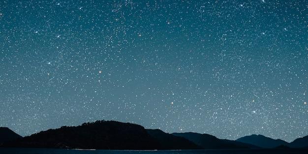 배경 별 하늘에 달은 바다에 반영됩니다.