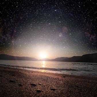海に映る星空を背景にした月