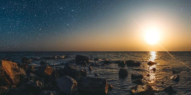 Месяц на фоне звездного неба отражается в море.