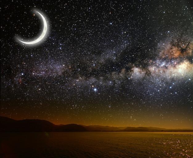 Месяц на стене звездного неба отражается в море.